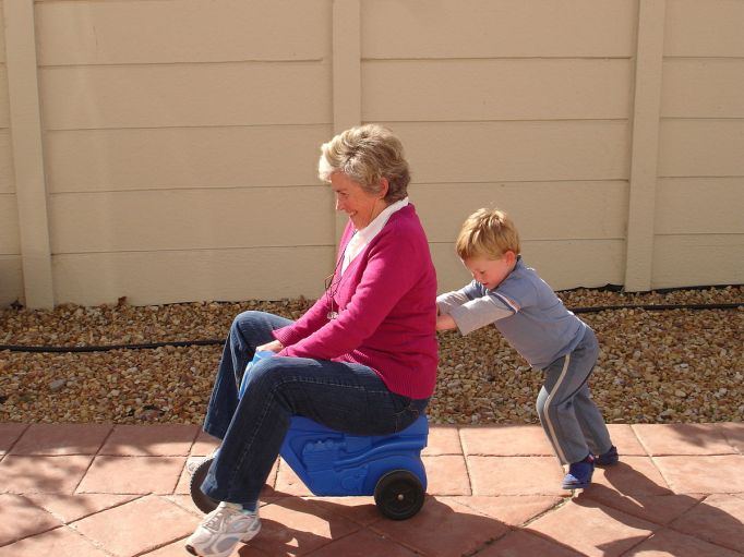 1200px-Child_pushing_grandmother_on_plastic_tricycle